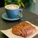 Pain au Chocolat (Foreground), Flat White (Background)