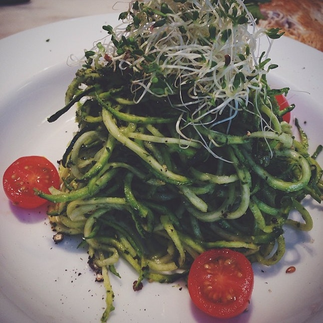 Raw Zucchini Pesto Pasta topped with generous portion of alfalfa sprouts.