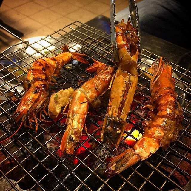 Grilling prawns over charcoal Vietnamese way.