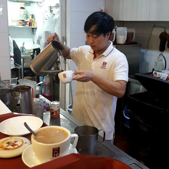 Yakun Barista dude pouring out another cup of joe.