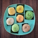 """""""Ang Kuh Kueh tasting 2"""" ・ 📌Poh Cheu Soon Kueh and Ang Kuh Kueh ・ 前回12種類中7種類を食べたので、今回は残りの5種類とお気に入り2種類の計7つを食べ比べ。  左中段から時計回りにマンゴー、ドリアン、パイナップル、ココナッツ、コーヒー、緑茶で真ん中があんこです。  あんこはこしあんでまさに和菓子のようで、日本人に馴染むみのある味でした。  フルーツ系は、実はわたしがお菓子に入ってるフルーツジャムが苦手なわたしにとっては、もう2回目はいいかなって言うのが本音です。  ココナッツはよくある奇抜なオレンジ色ではなく自然な色味で食感もあるので、好き嫌いは分かれそう。  12種類もあるので、ぜひお好みのフレーバーを探してみてくださいね。  少し投稿に間が空いてしまいましたが、過去の投稿に残りの7種類についてもアップしてます。 またブログでもJi Xiang Ang Ku KuehとこちらのPoh Cheuのアンクークエを紹介しています。プロフィール @dorimingo813 のURLから飛べるので、よかったら覗きにきてくださいね。  #angkukueh #pohcheu @pohcheukitchen #アンクークエ #ニョニャ菓子 #ニョニャ #nyonya #シンガポールグルメ #シンガポール #シンガポール生活#singaporelife #シンガポール在住 #シンガポール旅行 #lovesg #singapura #シンガポール子育て #singaporeinsiders #singaporeinsta #igsg #🇸🇬 #sgfood#sgeats#sgfoodies#foodpics#burpple#sgfoodporn#eatoutsg#みど散歩"""