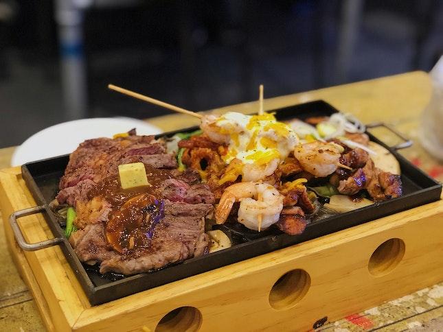 all in - beef steak, prawns, grilled pork, mac & cheese, garlic tortilla, bread rolls, coleslaw & salad