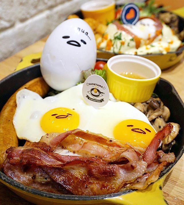 """Big """"Nua"""" Breakfast ($25.90) Hearty portions of crispy bacon & lazy sunny sides up topped on buttery brioche toast, paired with spicy pork bratwurst & sautéed mushrooms."""