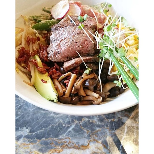 A bowl of brown rice with beansprouts, avocado, snap beans, sweetcorn, mushrooms, tomatoes, doumiao and short beef ribs off the bone.