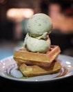 Waffles with 2 scoops of their premium pistachio ice cream .