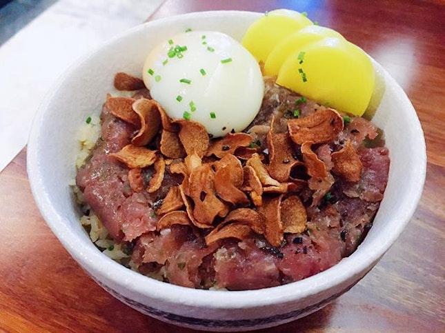 Tanuki Raw  Negitoro Don $14.90+  Chopped fatty tuna and scallions seasoned with black garlic and roasted leek soy, onsen egg over Tanuki's signature mixed rice.
