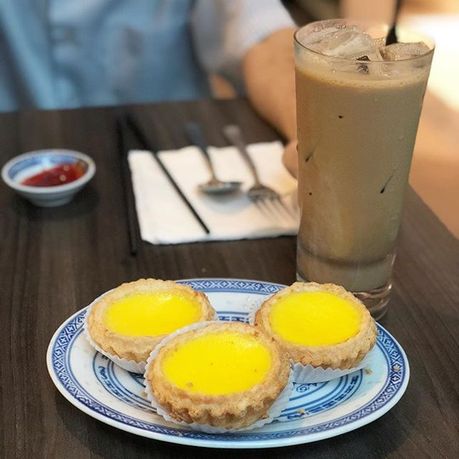 Life's simple pleasures - flakey hot egg tarts and iced milk tea from @honolulucafesg.
