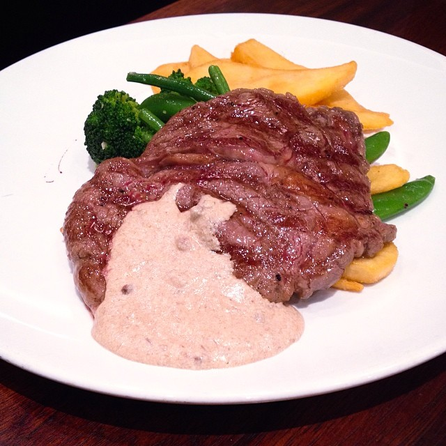 "Char-grilled ribeye with ""pink peppercorn"", served with fries and spring vegetables."