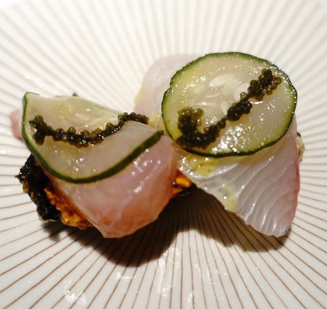 Pescado con Romesco, Japanese kingfish or yellowtail served with romesco, pickled cucumbers and seaweed crackers.
