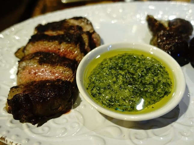 Rangers valley striploin, medium rare served with chimichurri and potatoes.