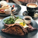 Savoury French toast ($16)  Fluffy brioche toast served with baked bacon, a sunny side up egg, homemade TCA house blend espresso golden syrup, and a side of seasonal greens.
