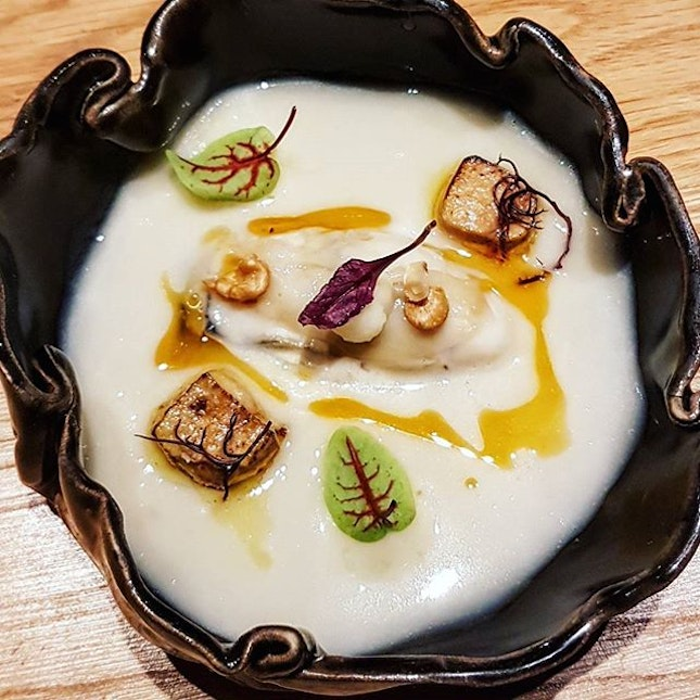 Gently poached, sweet, pristine oyster tucked into a bath of creamy Jerusalem artichoke soup with a couple of cubes of seared foie gras on top...