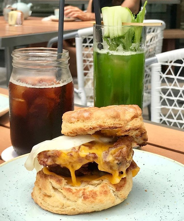 Breakfast set of Chicken Biscuit Sandwich, paired with Green Veggie juice and an iced black