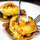 [Ash & Elm] - Poached Eggs doused in a creamy hollandaise sauce atop bacon, spinach and English muffin.
